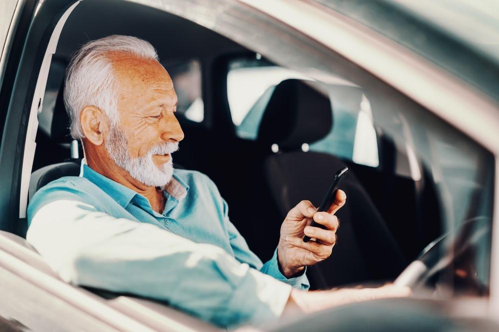 Old man looking at his phone in the car